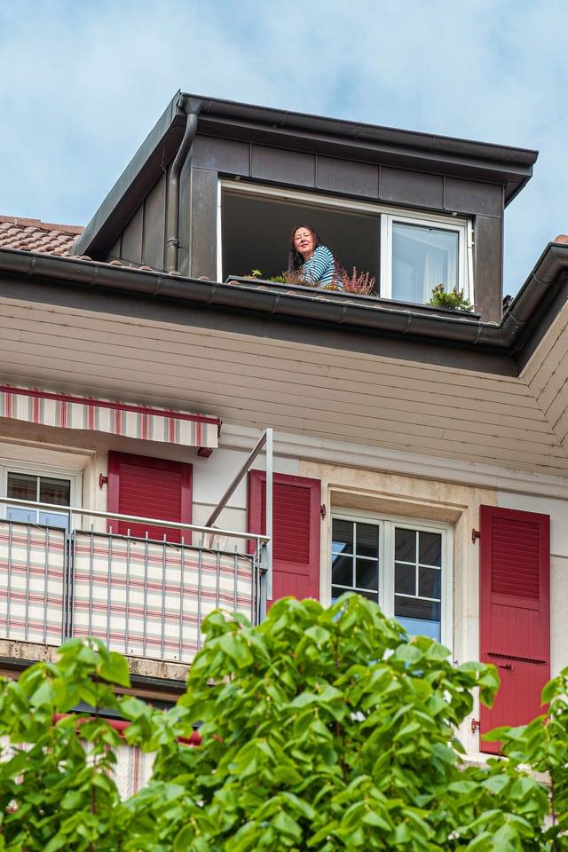 Eine Frau sitzt an ihrem Dachfenster und blickt zum Fotograf hinunter.