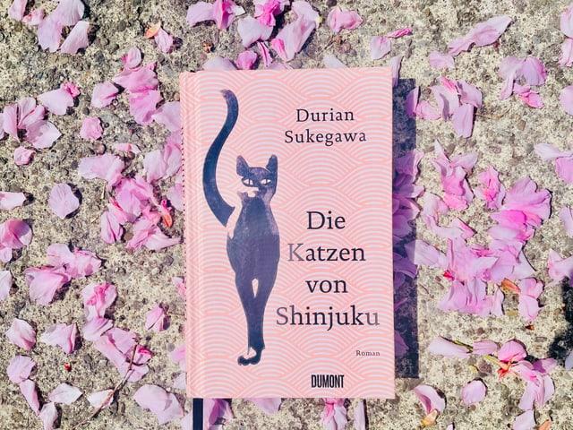 Der Roman «Die Katzen von Shinjuku» von Durian Sukegawa liegt auf Kirschblüten