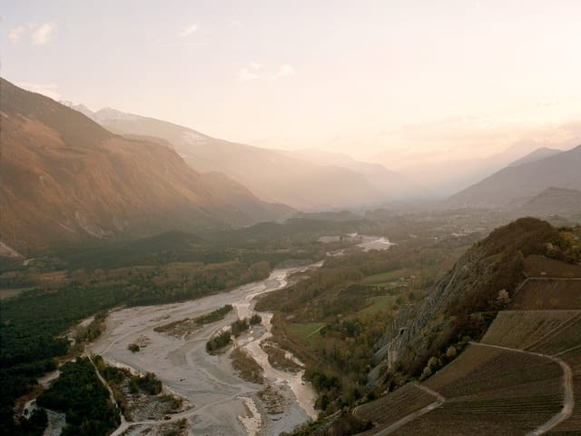 Blick aus der Höe auf ein Tal mit einem Fluss mit vielen kleinen Nebenläufen.