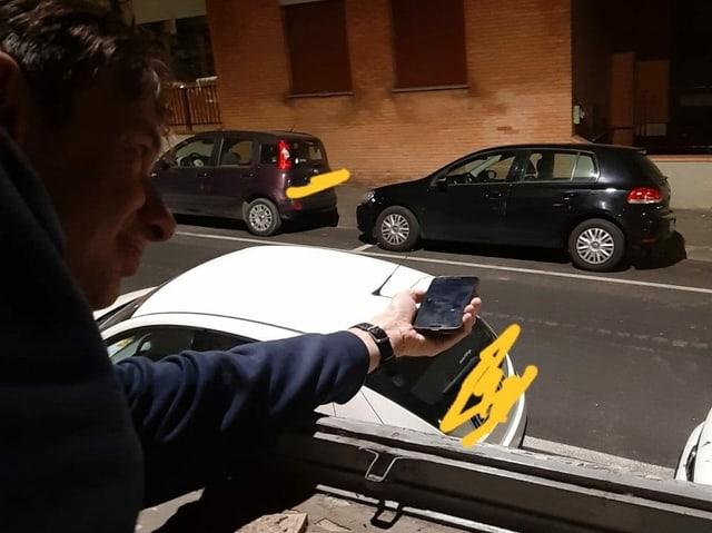 Mann in Italien streckt Handy aus dem Fenster, um Lichtstrahlung zu messen.