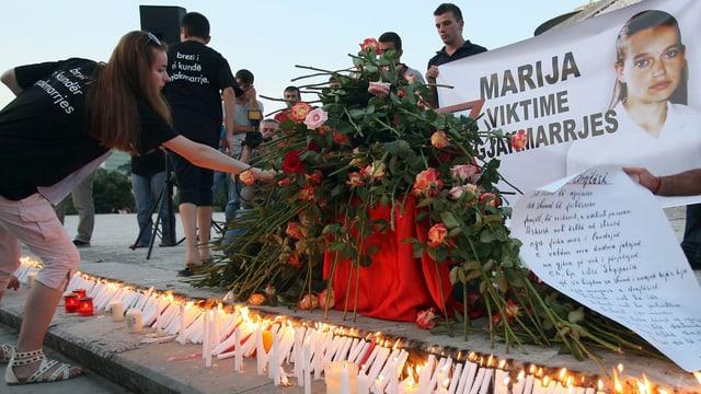 Eine Frau legt Blumen nieder vor einem Plakat mit dem Gesicht einer Jugendlichen drauf.