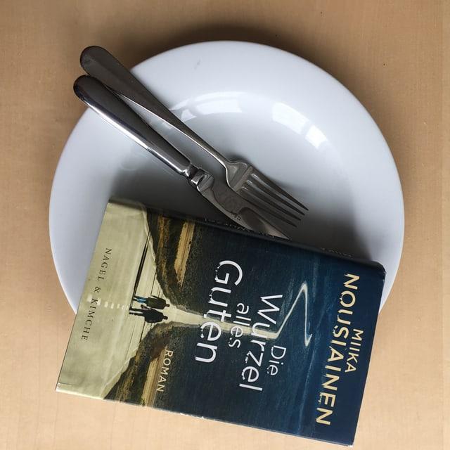 Der Roman «Die Wurzel alles Guten» liegt auf einem weissen Teller. Messer und Gabel drunter.