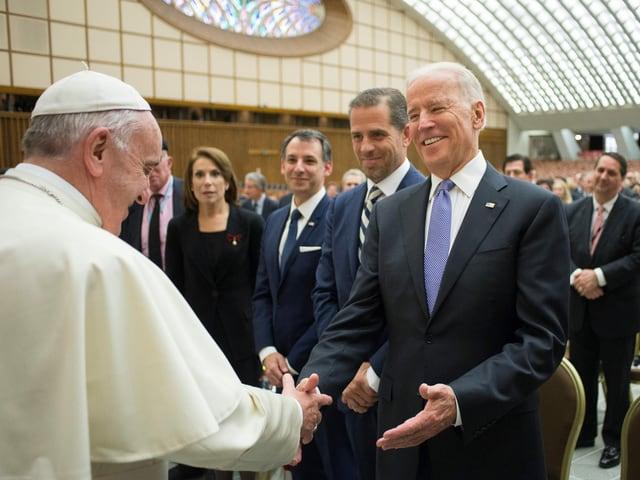 Ein Papst und ein Mann begrüssen sich freundlich mit Handschlag.