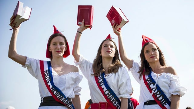 Drei Frauen als Marianne verkleidet halten jeweils das französische Gesetz in der Hand
