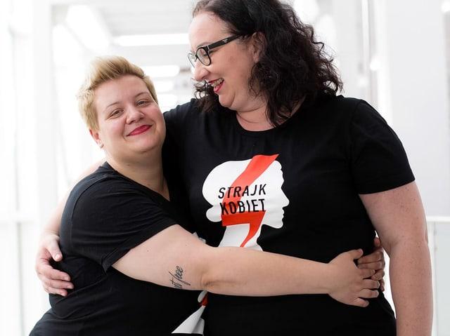 Zwei jüngere Frauen in schwarzen T-Shirts umarmen sich und lachen.