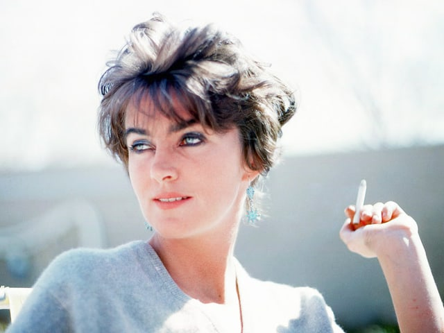 Lucia Berlin blickt zur Seite und raucht.