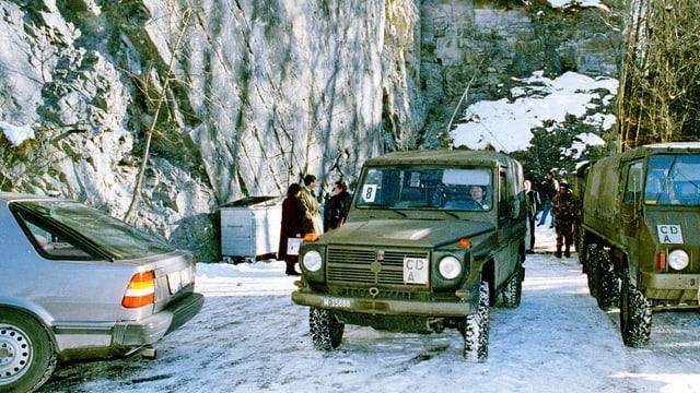 Vor der unterirdischen Bunkeranlage bei Gstaad: grüne Jeeps parken vor einem Gebirge.