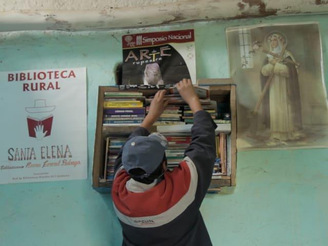 Ein Junge nimmt ein Buch aus dem Regal einer sogenannten Wolkenbibliothek - der Bestand umfasst häufig nur wenige Bücher.
