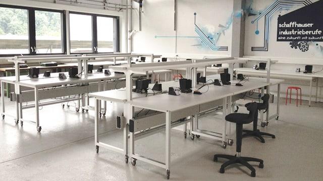 Ein Labor mit Tischen und technischen Materialien.