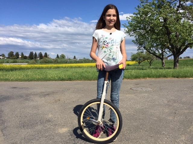 Tabitha steht hinter ihrem Einrad und lacht in die Kamera