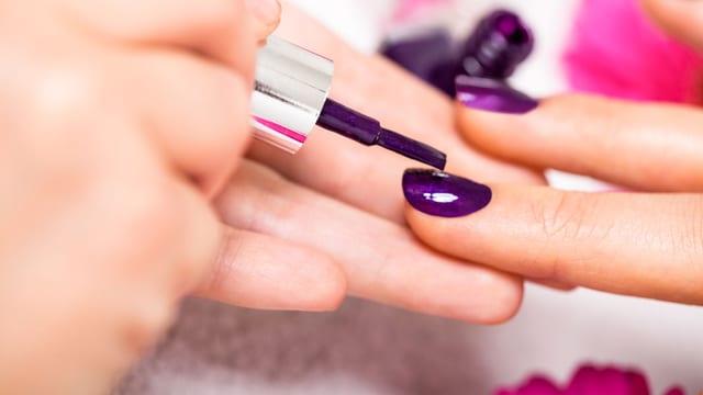 Eine Frau streicht einer anderen die Fingernägel mit violettem Lack an.