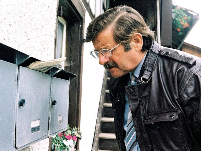 Ein Mann mit Brille und Lederjacke steht vor einen Briefkasten.