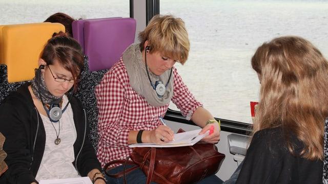 Studenten sitzen mit Kopfhörern im Zug, See im Hintergrund
