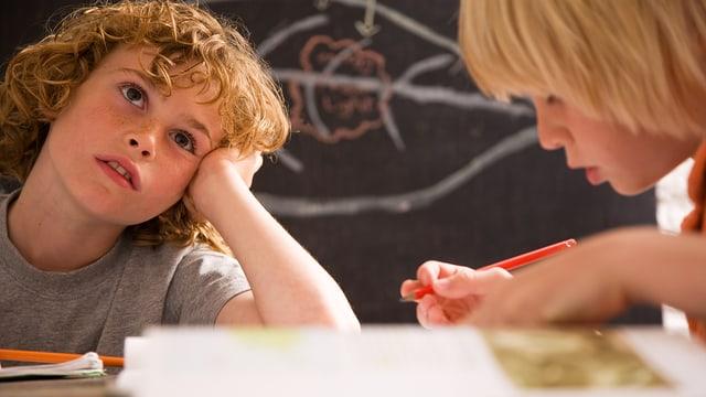 Zwei Kinder sitzen über Schulbüchern.