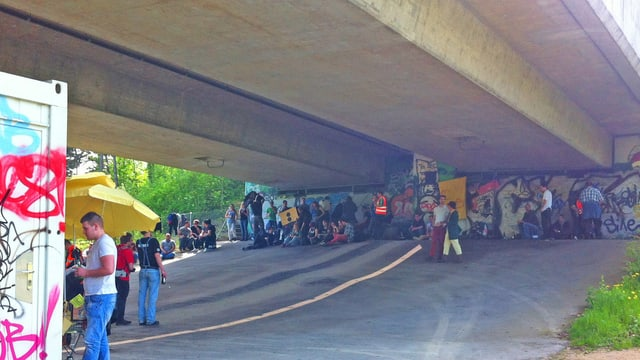 Jugendliche feiern unter der Brücke.