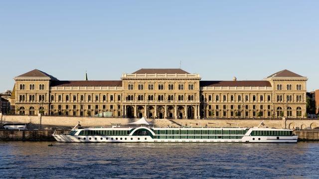 Ein Boot auf einem Fluss und im Hintergrund ein Gebäude.