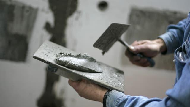 Ein Maurer hat eine Maurerkelle in der Hand mit Mörtel darauf.