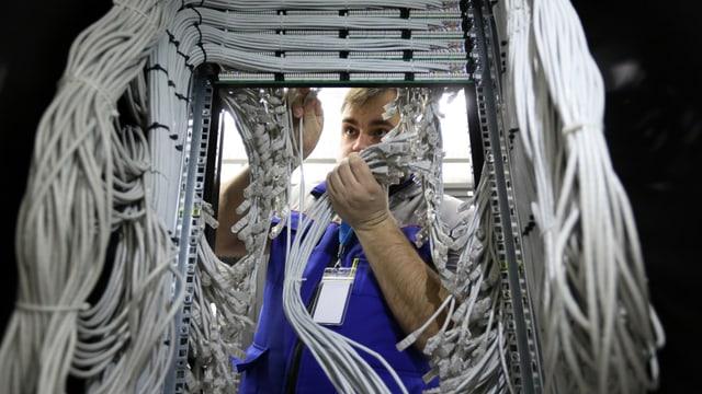 Ein Mann steht inmitten vieler Kabel.