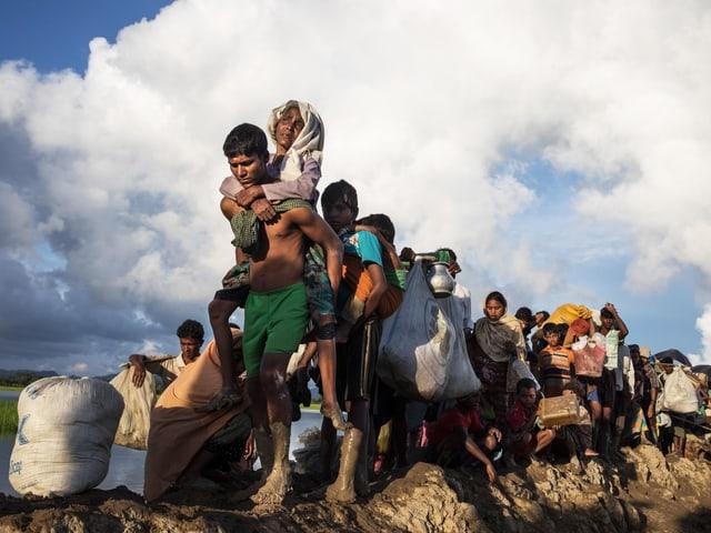 Rohingyas auf der Flucht: Eine Gruppe Menschen geht hintereinander, vorne trägt ein Mann eine alte Frau.