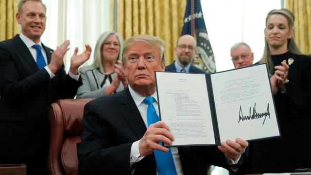 Trump hält Vertrag in die Höhe.