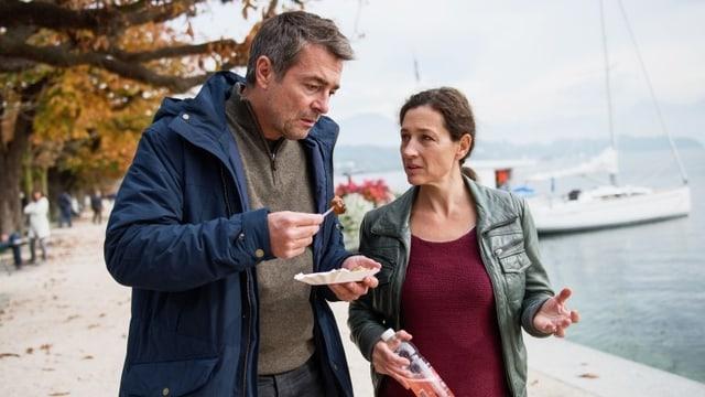 Stefan Gubser und Delia Mayer stehen am Seeufer. Gubser isst Fastfood, im Hintergrund ein Segelboot.