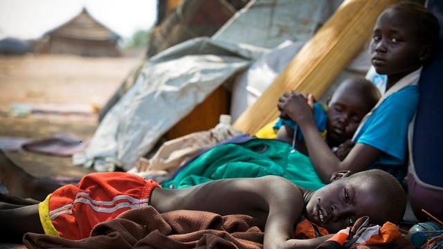 Kinder in Flüchtlingslager, Im Hintergrund sind die verschwommenen Umrisse eines Gebäudes erkennbar