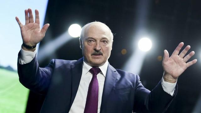 Lukaschenko hat beide Hände erhoben und blickt in die Ferne.