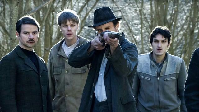 Ein paar Männer stehen in einer Gruppe zusammen. Einer trägt eine Waffe und ziehlt damit.