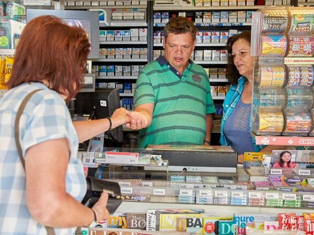 Ein Mann kassiert Geld ein an einem Kiosk