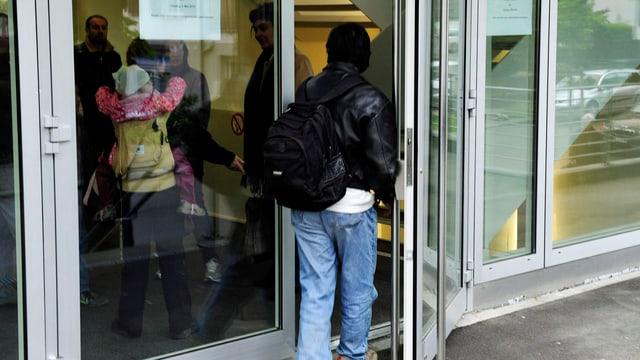 Ein Mann mit dunkelbrauner Haut betritt das Zürcher Migrationsamt.