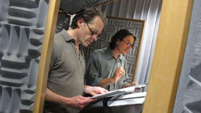 Blick durch die Tür ins Hörspielstudio auf Oliver Sauer und Till Kretzschmar mit Manuskript in der Hand vor dem Mikrofon.