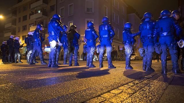 Polizisten aufgereiht auf der Strasse riegeln eine Strasse ab.