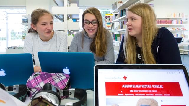 """3 Teenagerinnen an einem Tisch mit 3 Laptops, auf einem wird die Webseite von """"Abenteuer Schule"""" angezeigt."""