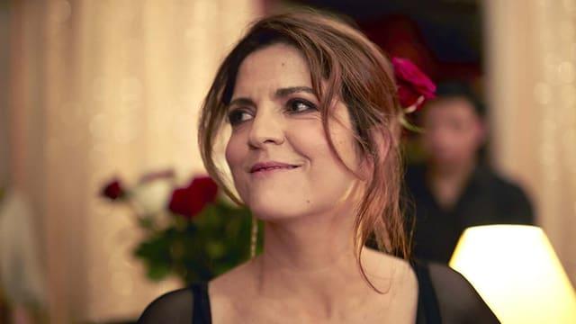 Aurore trägt eine rote Rose im Haar und blickt lächelnd an der Kamera vorbei.