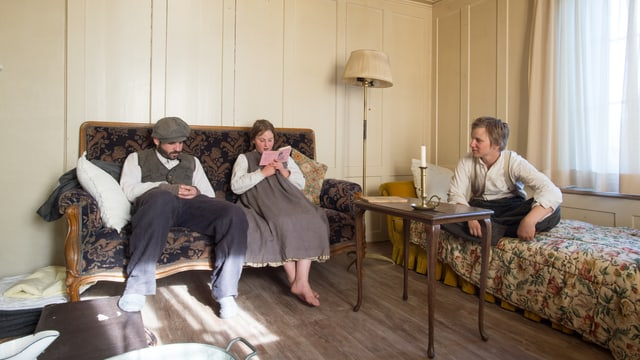 Fabio, Alenka und Merlin in Stube im Kosthaus, Alenka liest aus einem Buch vor