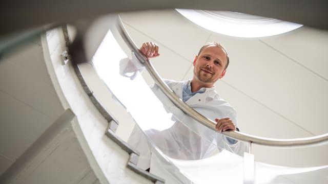 Porträt Collin Ewald, der von einer Wendeltreppe runterblickt.