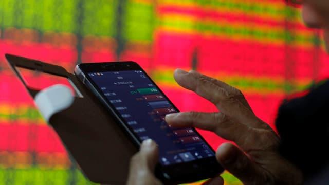 Mann sieht sich auf Handy die Aktienkurse an.