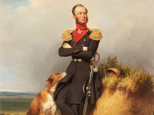 Ein Mann lehnt an einem Hügel, ein Jagdhund schaut zu ihm auf.