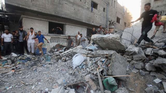 Trümmer in den Strassen von Gaza-Stadt. Leute klettern darauf herum.