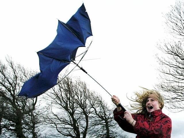 Ein blauer Schirm in der Hand eines Mädchen klappt im Sturm um.