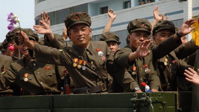 An einer Parade winken nordkoreanische Soldaten den Zuschauern mit Orchideenzweigen zu.