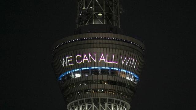 Tokios Turm verbreitet positive Nachrichten: «Together We Can All Win» (engl. für: Zusammen können wir alle gewinnen.)