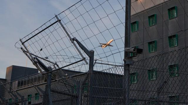 Ein Flugzeug über den Dächern des Gefängnisses am Flughafen Zürich.
