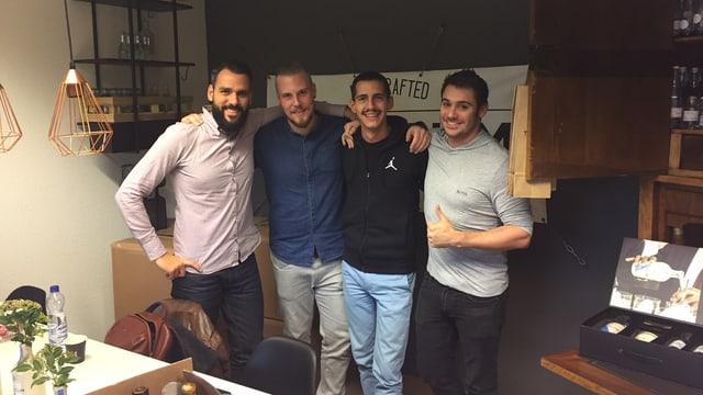 Vier junge Männer stehen in einer Reihe und umarmen sich