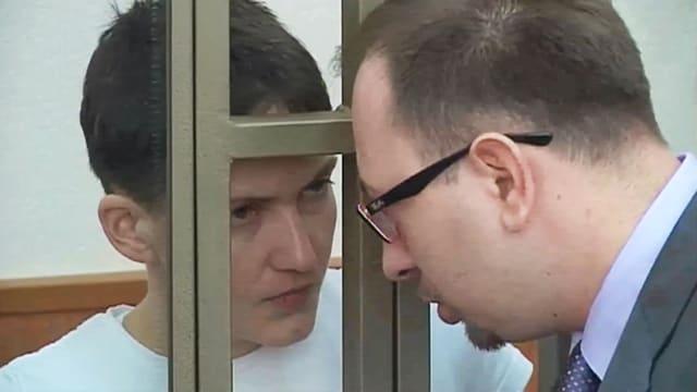 Sawtschenko bespricht sich mit ihrem Anwalt. Die verurteilte Pilotin befindet sich im Gerichtssaal hinter Gittern. (reuters)