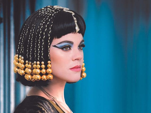 Eine Frau, die stark geschminkt ist, trägt viel Schmuck in ihren halblangen schwarzen Haarem.