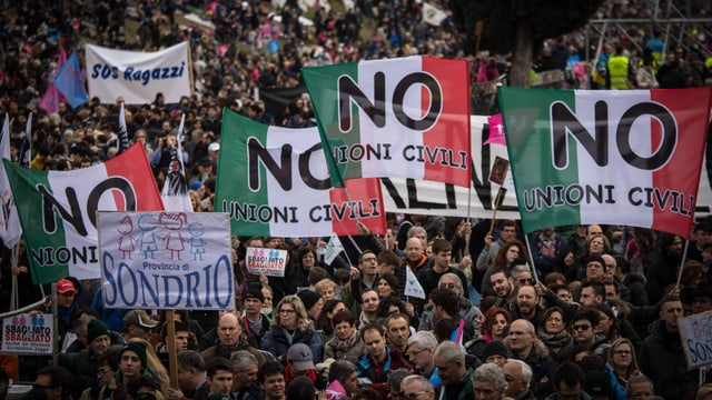 Menschen protestieren mit Bannern.