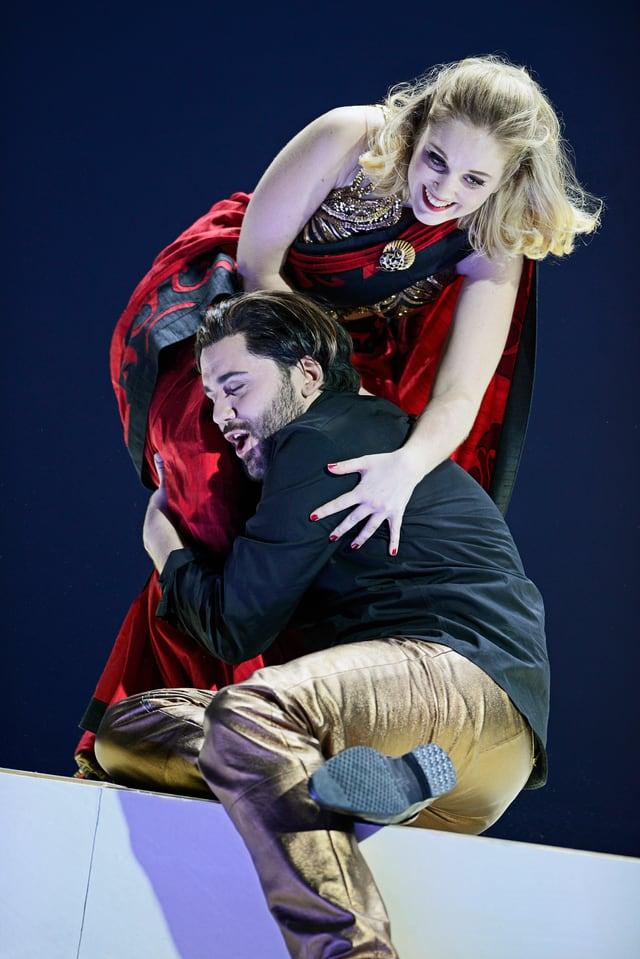Opernsängerin und -Sänger auf einer Bühne. Er, sitzend, hält ihre Beine fest.