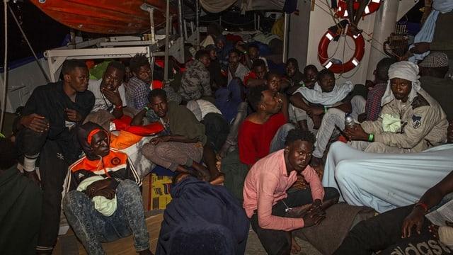 Flüchtlinge sitzen in der Nacht auf dem Schiffsdeck.