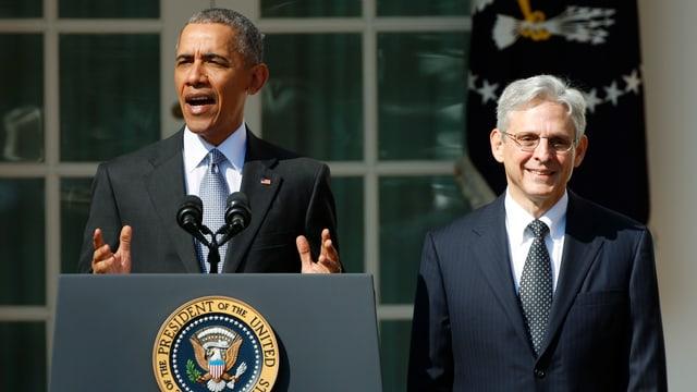Barack Obama (links) an einem Rednerpult vor dem Weissen Haus. Rechts daneben steht Merrick Garland.